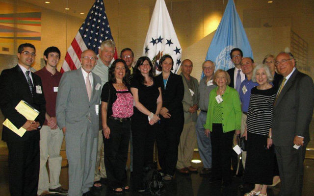 MetroWest Community Relations Committee delegates met with United States Foreign Service officer Barbara Masilko, center, in front of white flag, at the U.S. Mission to the United Nations. Photo by Robert Wiener
