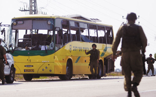 Israeli soldiers outside a school bus that was hit by a rocket near Sderot from the Gaza Strip, injuring two, including a teenager seriously, April 7. Photo by Dima Vazinovich/Flash90/JTA