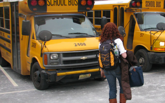 A student at Solomon Schechter Day School of Essex and Union in West Orange heads for a school bus in the parking lot. State transportation aid to families of parochial school students has been spared from state budget cuts.