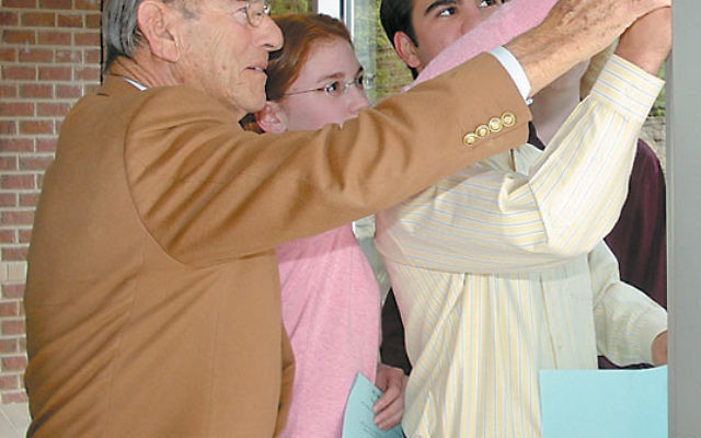 Eric F. Ross helps affix a mezuza to the entrance to Solomon Schechter Day School of Essex and Union's upper school in West Orange in 2008 at the school's rededication following a renovation. Photo courtesy SSDSEU