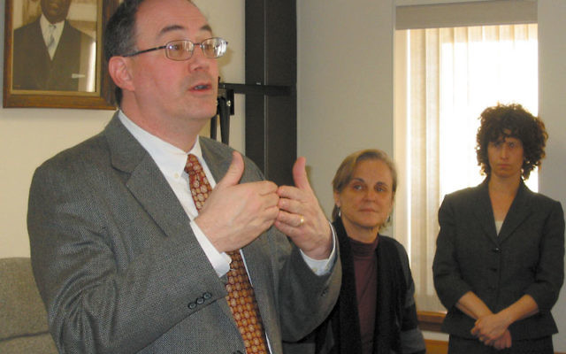 Reuben Rotman, Jewish Family Service of MetroWest executive director, announces the $100,000 gift from Anita Fishman to the Rachel Coalition's court advocacy training program at the final session of the fall training, held Dec. 8 in Newark. Lookin