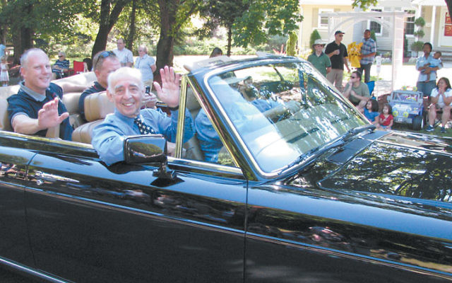 Waving to the crowd from the front seat of a Rolls Royce convertible, Jack Schrier greets constituents during the 2008 Labor Day parade in his hometown of Mendham. Photo by Robert Wiener