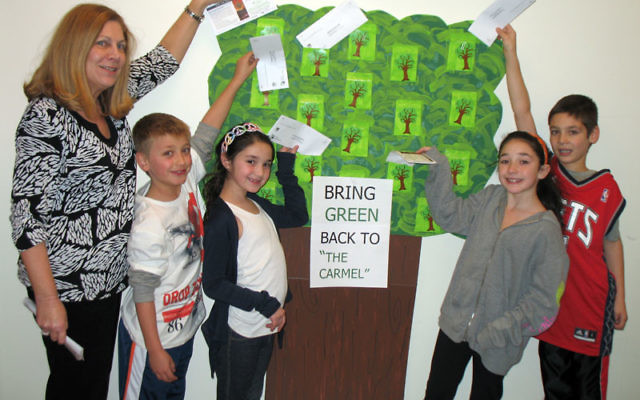"""Contributing to Temple B'nai Abraham's """"Bring Green to the Carmel"""" project are, from left, TBA religious school director Janet Resnick and students Josh Greenberg, Hallie Goldberg, Lara Klein, and Evan Marcus. Photo courtesy Temp"""