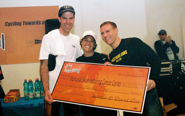 Jennifer and Dave Linn, right, present Dr. Robert Maki of Memorial Sloan-Kettering Cancer Center with a check following the inaugural Spin4Survival in January 2007.