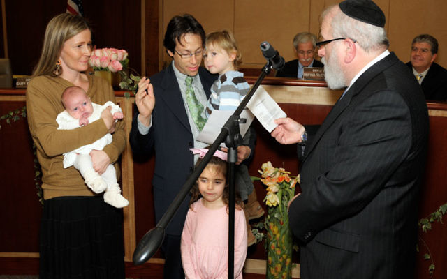 Rabbi Shlomo Krupka of Congregation Etz Chaim administers the oath of office to Michael Rieber, who is joined by his family, wife Sarah holding Sasha, Emma, and Jonah. Photos by Bob Krasner