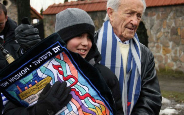 A day before his bar mitzva Zachary Karger carries a Torah scroll that his grandfather, Ed Mosberg, right, retrieved after it had been seized by the Nazis during World War II.