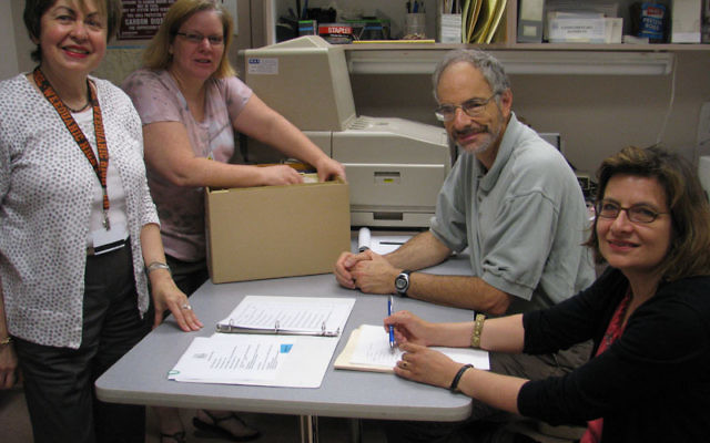 Jewish Historical Society of MetroWest executive director Linda Forgosh, left, and archivist Jill Hershorin present the supermarket archives to Ronald Becker and Fernanda Perrone of Rutgers University's Alexander Library. Photos by Robert Wiener