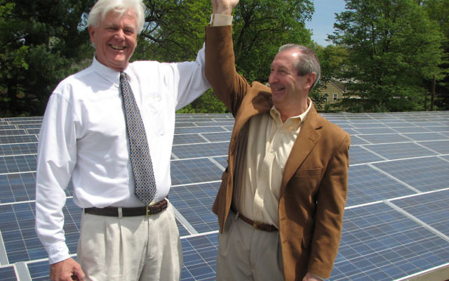 Charles Wantman, right, and Don Powell show off their handiwork in a visit to the Oheb Shalom roof following the solar panel dedication ceremony.