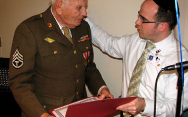 Alex Gross, administrator of the Lester Senior Housing Complex, presents a certificate of appreciation to former army sergeant and World War II veteran Alex Glass.