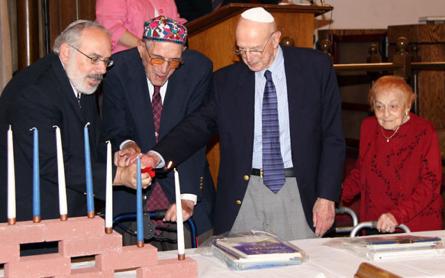 Rabbi David Nesson, left, lights candles with three of the congregation's oldest members, from left, Harold Krauss, Herman Frigand, and Rookie Friedman. Photo courtesy MJCBY