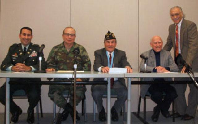Telling their war stories are, from left, veterans Marc Krauss, Arthur Weintraub, Myron Katz, and Bob Max, while Jewish Historical Society president Howard Kiesel looks on.