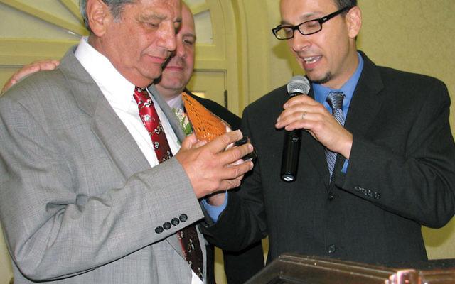 Weequahic High School Alumni Association cofounder Sheldon Bross receives a testimonial trophy from his son Michael. Photos by Robert Wiener