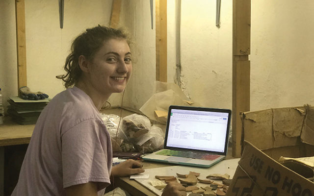 """Elana Neher identifying objects """"lost"""" in the attic of an archaeological research institution in Israel. Photos courtesy Johns Hopkins University"""