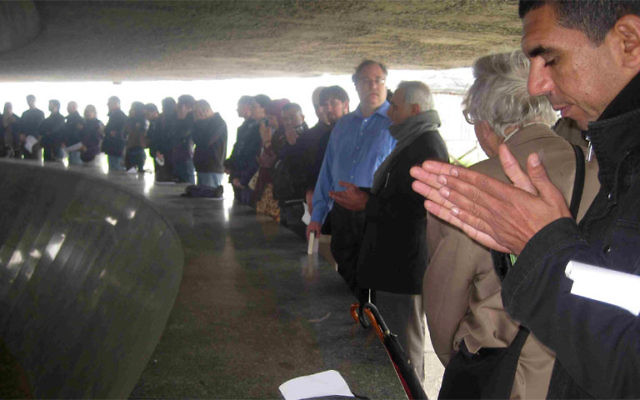 Visitors to Majdanek, including Rabbi Alan Brill, fourth from right, pay homage to the victims of the Nazis.
