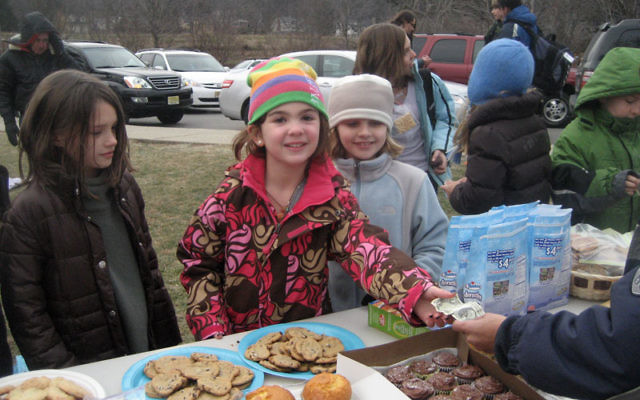 Madison Schuckman, eight, in striped hat, completes a transaction at the bake sale she held at Wildwood Elementary School in Mountain Lakes on Dec. 16 to raise funds for victims of the Carmel Forest fire. Photo courtesy Schuckman family