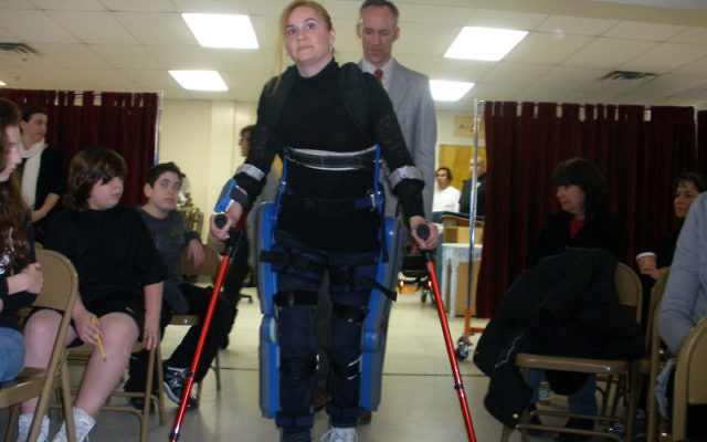Agnes Fejerdy, who was left a paraplegic after a car accident more than six years ago, demonstrates to students and staff at the Solomon Schechter Day School of Greater Monmouth County how she walks with the aid of the ReWalk. Behind her is Thomas C. Coul