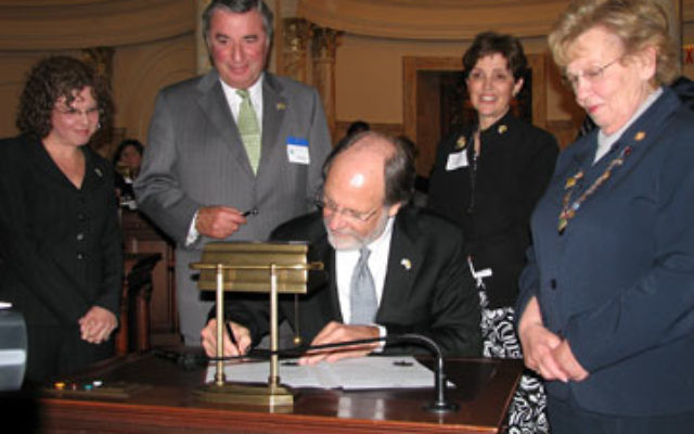 Gov. Jon Corzine signs a proclamation in May 2008 designating May as New Jersey-Israel Sister State Month. Looking on are, from left, Andrea Yonah, Leonard Posnock, and Marlene Herman of the New Jersey-Israel Commission; and state Sen. Loretta Weinberg.