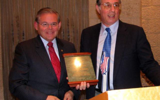 Sen. Robert Menendez recieves an award from Lionel Kaplan, vice president of United Jewish Federation of Princeton Mercer Bucks, right, following the senator's speech.