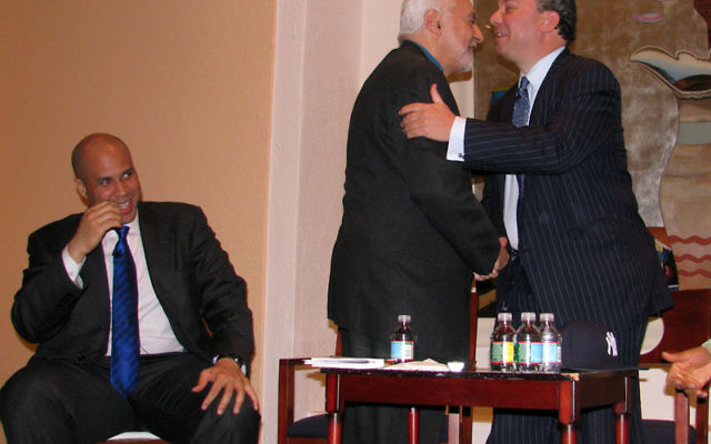 """Rabbi Marc Schneier, right, greets Imam Feisal Abdul Rauf at """"a conversation on the Black/Jewish Alliance"""" in the Newark Museum. Mayor Cory Booker, left, looks on. Photos by Robert Wiener"""