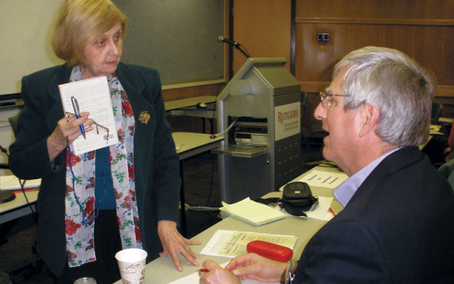 Tova Friedman of Highland Park speaks to Holocaust scholar Christopher R. Browning while she holds a copy of his book, Remembering Survival: Inside a Nazi Slave-Labor Camp. Friedman — then known as Tola Grossman — as a five-year-old w