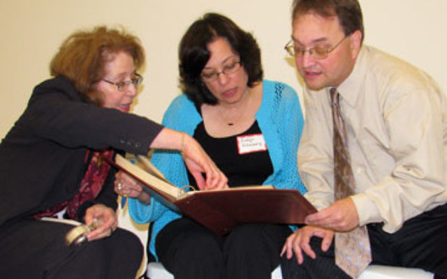 Monica Hartman, left, and siblings Evelyn Altenberg and Les Altenberg, children of Holocaust survivors who found refuge in Latin America, look at a photo album of survivors in the Dominican Republic.