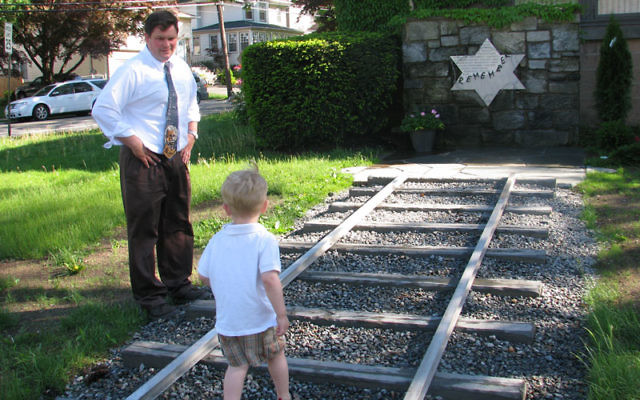 Mark Russo and his three-year-old son, Mason, view the Holocaust memorial outside Congregation Beth Ahm.