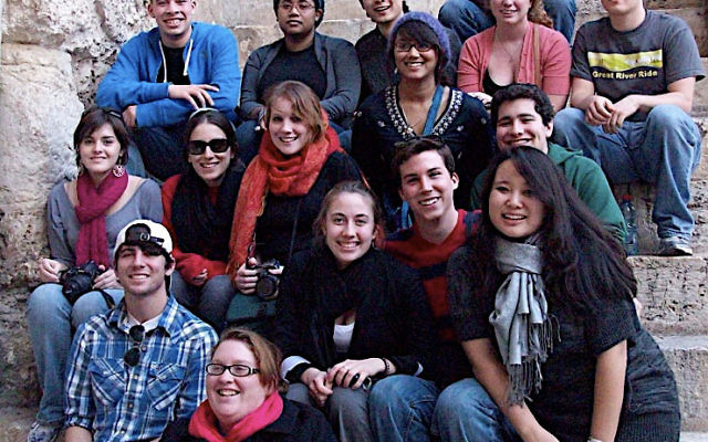 Project Interchange students sit on the steps outside the Church of the Holy Sepulcher in Jerusalem. Brian Solomon, smiling, is seated on the far right of the third row from the bottom. Brian No, wearing glasses, is seated on the left of the next to last