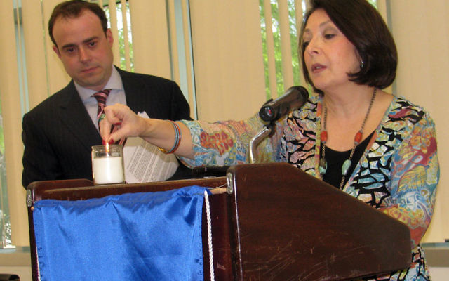 Etzion Neuer, director of the Anti-Defamation League's New Jersey region, watches Barbara Wind, director of the Holocaust Council of MetroWest, light a memorial candle for Sister Rose Thering. Photo by Robert Wiener