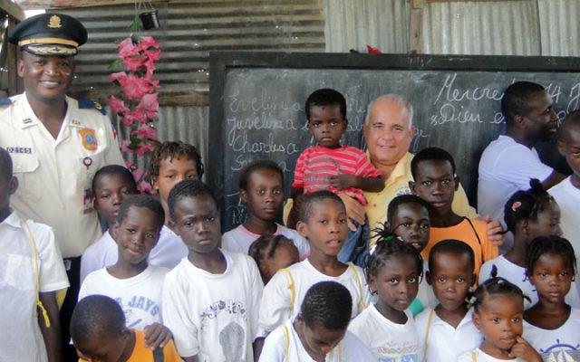 Alan Goldsmith, president of the Jewish Renaissance Medical Center and Foundation, is surrounded by children at the Tabarre School near Port-au-Prince, which the foundation has adopted. With them is national police commissioner Justin Marc, far left. Ph