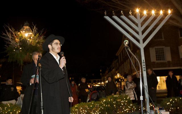Rabbi Levi Dubov addresses the crowd at the Chabad of Mercer County Hanukka celebration in Princeton last year.