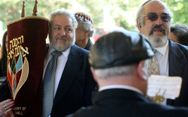 Robert Pearson, left, carries the Torah scroll into the synagogue as Rabbi Daniel Grossman, right, and clarinetist Steven Kaplan proceed into the synagogue for the dedication.