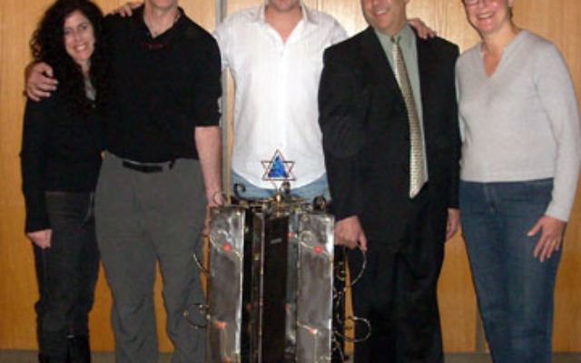 Gary Rosenthal, second from left, designed the tzedaka box to mark The Jewish Center's 60th anniversary. With him are, from left, Naomi Perlman, 60th anniversary committee chair; Neil Wise, director of programming; Rabbi Adam Feldman; and H