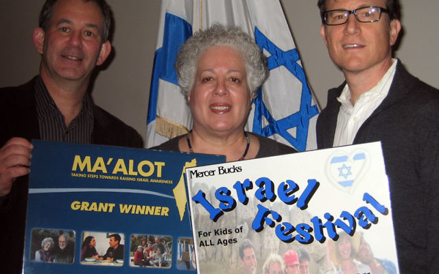 Displaying posters for Adath Israel's community Israel Festival are event cochairs Jonathan Miller, left, and Seth Park and director of congregational learning Hedda Morton. Photo courtesy Adath Israel Congregation