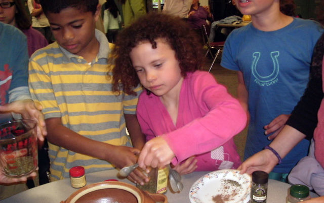 Students at String of Pearls' religious school prepare grape leaves for their snack.