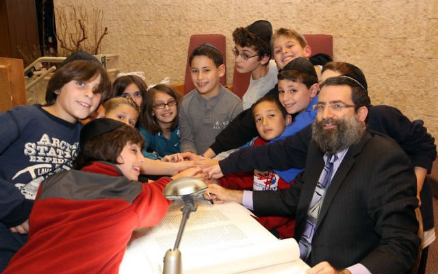 Children gather around sofer Moshe Druin as he inscribes letters in the Torah scroll, which is now housed in Congregation Shir Ami's chapel.