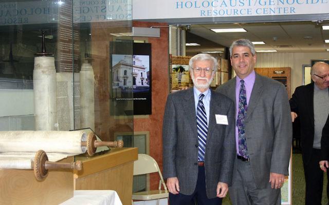 "Saul Goldwasser, left, director of the Mercer County Holocaust/Genocide Resource Center, and Rabbi Adam Feldman of the Princeton Jewish Center with the ""reunited"" Torah scrolls"