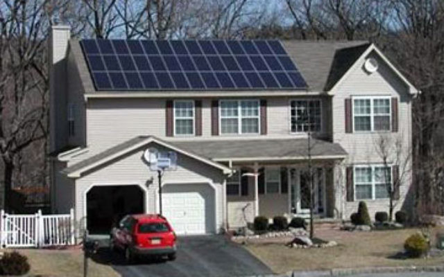 A Sun Farm Network solar panel provides energy for a house in the town of High Bridge.