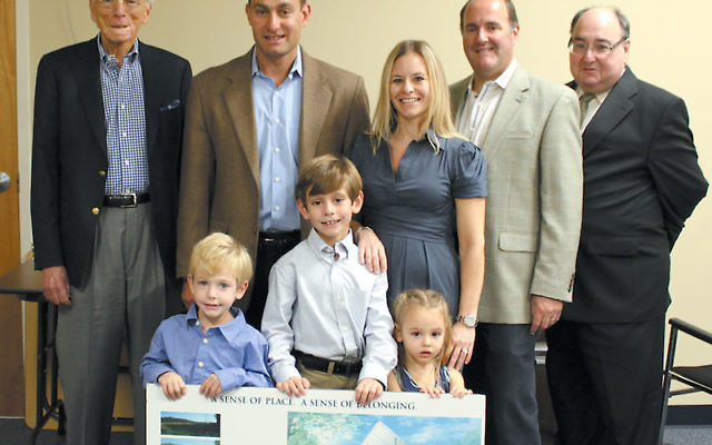 The Wilson family meet with Jewish Community Campus officials, from left, cochair Ron Berman, Matt and Staci Wilson, cochair Ron Berman, and executive director Drew Staffenberg, and, holding a board displaying pictures of the new campus, from left, Noah