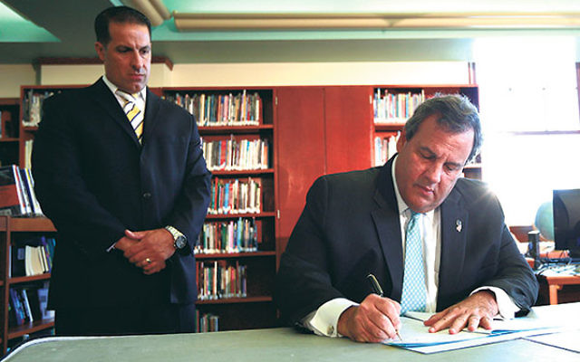 Gov. Chris Christie signs the Secure Schools for All Children Act into law.