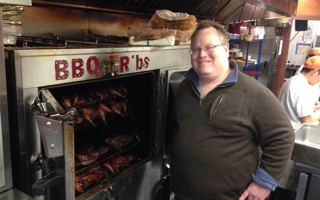 Joe Kessler-Godin mans the smoker at Smokey Joe's, his Tex-Mex barbecue joint in Teaneck. NJJN photo