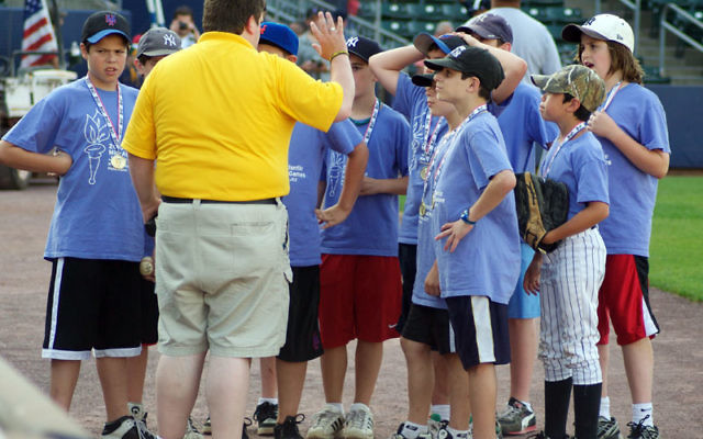 Members of the gold-winning MetroWest Junior Maccabi baseball team get instructions for the pregame ceremonies. Photos by Rachel Kaplan