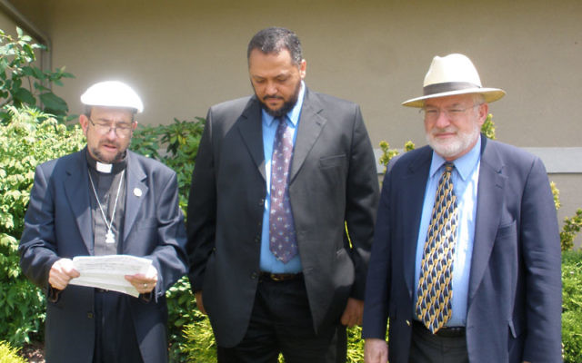 Rev. Kenneth J. Macari of the Community Presbyterian Church in Edison, left, reads a prayer for peace and guidance for President Barack Obama outside Congregation Beth-El in Edison. Looking on are Imam Moustafa Zayed of the Islamic Society of Central Je