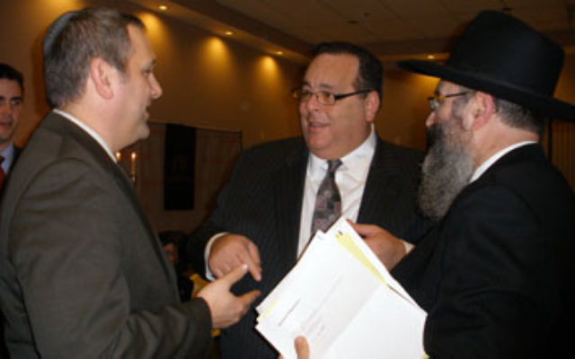 Rutgers Chabad executive director Rabbi Yosef Carlebach, right, greets deputy Israeli consul general Benjamin Krasna, left, and others at Chabad's Hanukka dinner on Dec. 17.