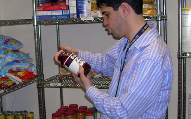 Volunteer Brian Raia of Edison helps stock the shelves of the kosher food pantry at the Jewish Family and Vocational Service of Middlesex County.