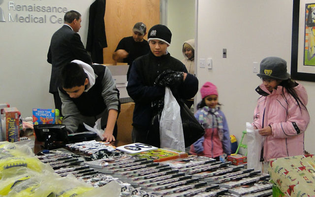 """Children and adults sort through mounds of gifts, toys, and sports equipment at """"the North Pole."""""""