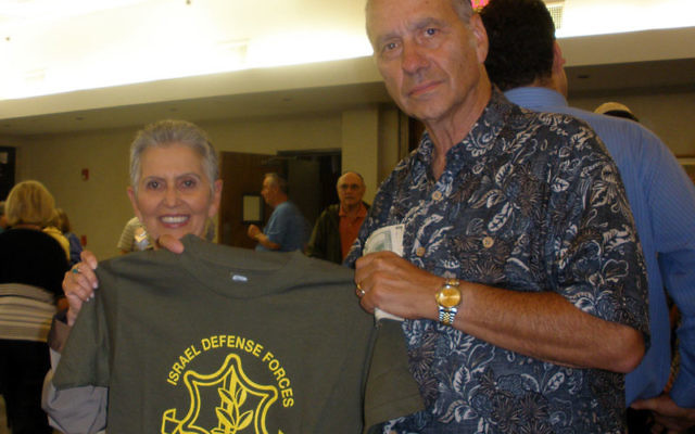 Ann and Paul Lerner of Somerset hold an IDF T-shirt sold at a Temple Beth El program to pay for such niceties as Shabbat meals for Israeli soldiers. Photos by Debra Rubin