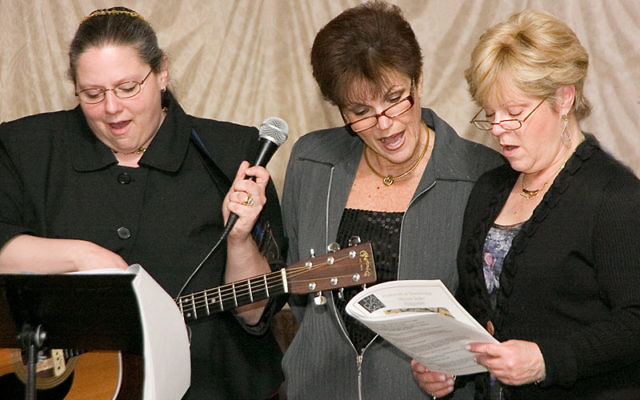 Reciting the Four Questions with Rabbi Melinda Panken, left, are Zahava Lievlich, center, and Rona Greenberg.