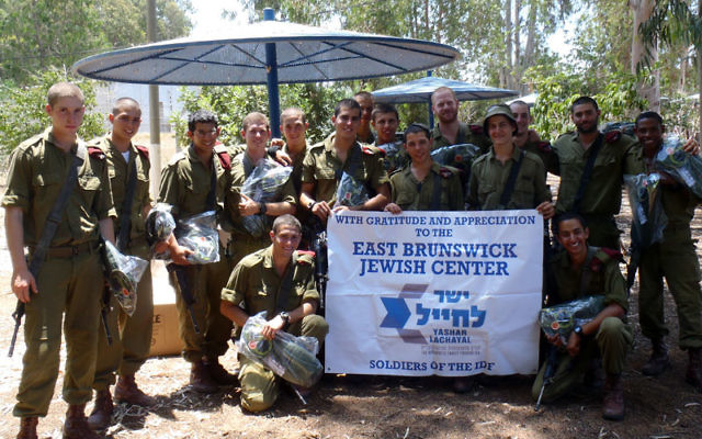 "Members of an IDF paratrooper unit thank the East Brunswick Jewish Center for a donation of water backpacks last month through Yashar LaChayal, which assists poor and ""lone"" soldiers."