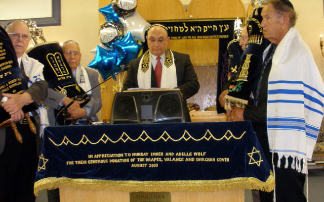 Cantor Eli Perlman leads a service celebrating the renaming of Congregation Beit Shalom, surrounded by synagogue members holding Torah scrolls.