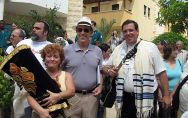 Estelle Marcus holds a Torah scroll donated by Congregation Neve Shalom to Sukkat Shalom, a Masorti synagogue. With her is Neve Shalom's Rabbi Gerald Zelizer, and, right, a Sukkat Shalom member.